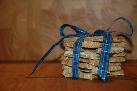 A stack of peanut butter dog treat recipes, tied up on a blue and gold ribbon, placed on a wooden board.